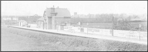 Neston South Station, circa 1950, viwed from the road bridge; note the train passing over the Station Road bridge heading for Neston North.