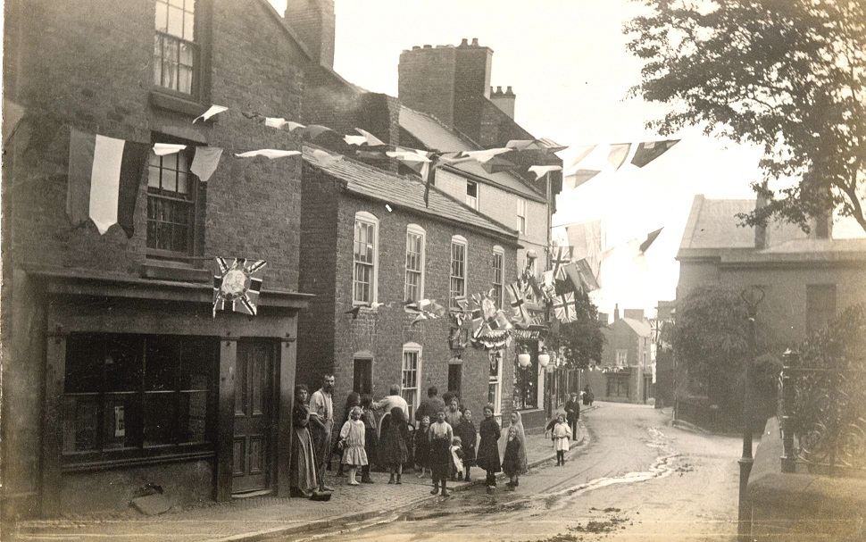 The people are standing at the entrance to Pykes Weint, probably at the time of the Coronation in 1911. The building on the left was Pykes in the 1770s. The building in the centre is the site of 'the chemist'.