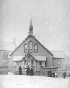 The iron Mission Hall, replaced in 1907 by Neston Methodist Church. Police station/Court House on the left.