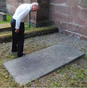 Ben Stephenson, a grandson of Billy Congreve, examining the memorial stone on the Congreve vault in Burton churchyard.