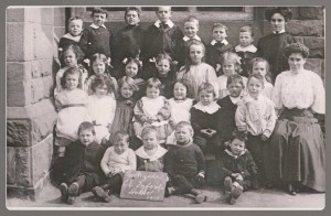 Parkgate Infant School, 1910 Back Row: the teacher far right is Miss Catherine Norman (David Scott's mother), Jim Bushell is standing next to her, far left is Monty Smith and third left is one of the Fewtrells. Next Row: Lizzie Bushell is the tall girl fifth on the left, next right is one of the Higgins', then Eva Bushell and teacher Miss Annie Bushell of Neston. Next Row: third from the left is Bet Fewtrell and next right is Mollie Bushell.